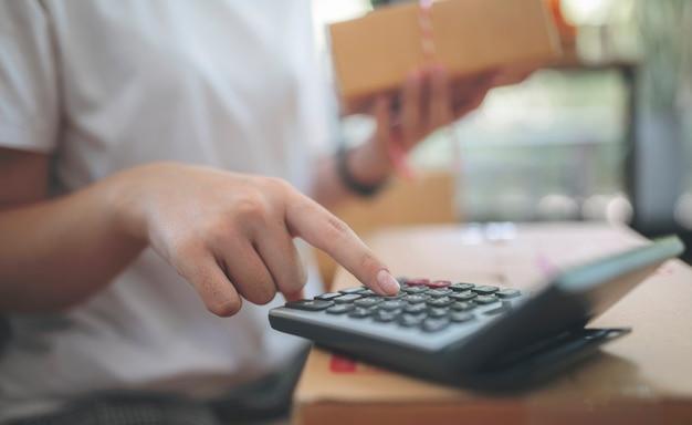 Femme travaillant sur la calculatrice.