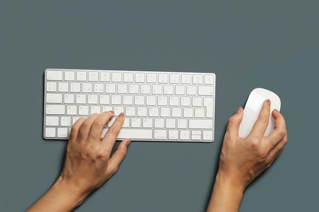 Femme travaillant sur un clavier moderne sur fond sombre