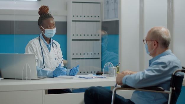 Femme travaillant comme infirmier discutant avec un vieil homme invalide