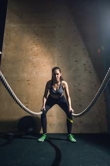Femme travaillant avec des cordes de bataille