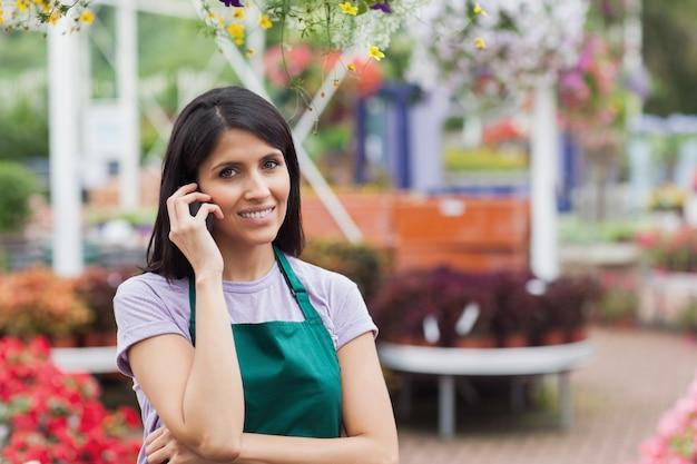 Femme travaillant dans une jardinerie faisant un appel