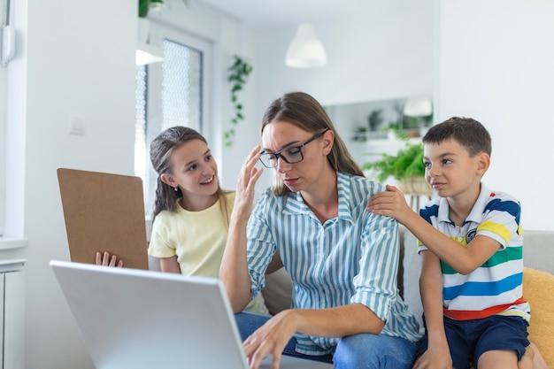 Femme travaillant à domicile pendant la quarantaine avec son petit fils et sa fille sur un canapé et criant, exigeant de l'attention