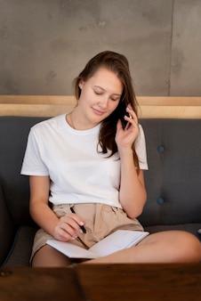 Femme travaillant à domicile avec smartphone