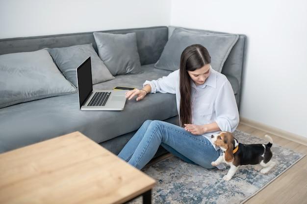 Une femme travaillant à domicile, son chiot jouant à côté d'elle