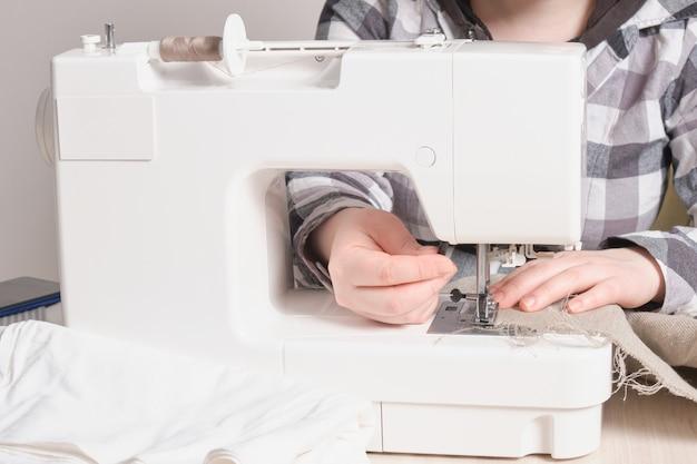 Femme travaillant avec une machine à coudre, une machine à coudre blanche sur la table, un processus de personnalisation des matériaux de couture face à l'espace