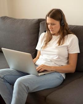 Femme travaillant à la maison sur le canapé pendant la quarantaine