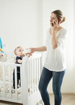 Femme travaillant à la maison et parlant par téléphone tout en nourrissant son bébé