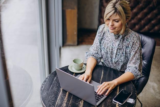 Femme travaillant sur ordinateur et buvant du café