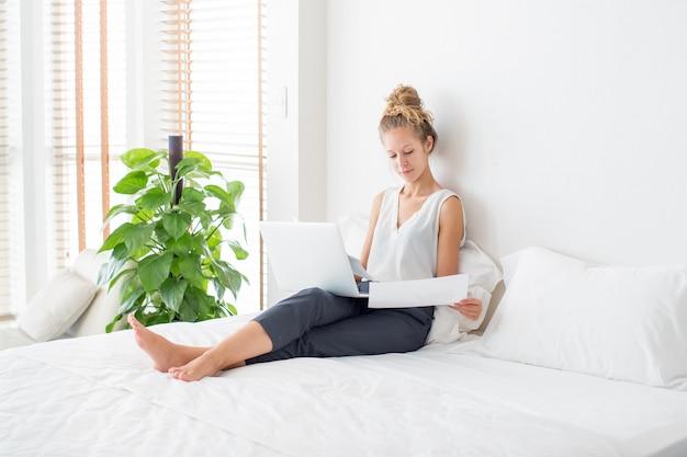 Femme travaillant sur ordinateur portable et assise sur un lit à la maison