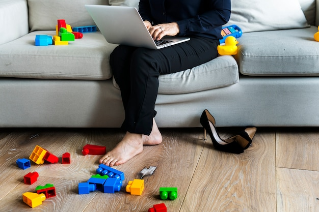 Femme travaillant sur un ordinateur portable sur un canapé