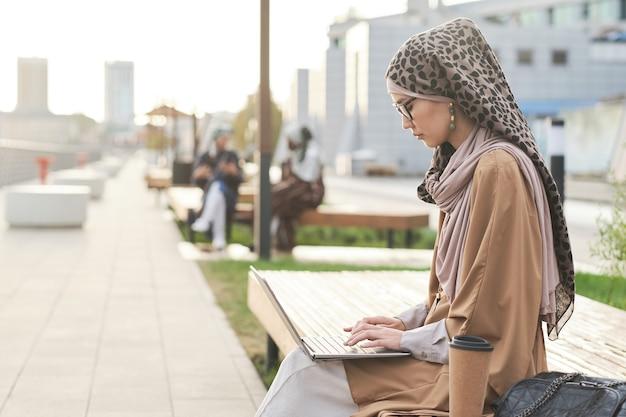 Femme travaillant sur ordinateur portable à l'extérieur