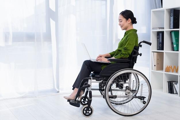 Femme travaillant sur ordinateur portable full shot