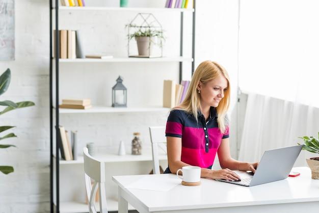 Femme travaillant sur ordinateur portable à la maison