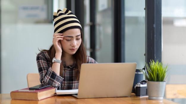 Femme travaillant avec ordinateur portable et papeterie sur table en bois dans un café