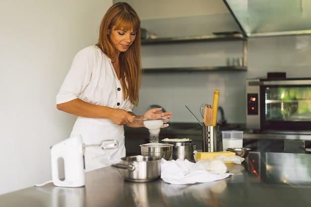 Femme travaillant avec une recette de préparation de pâte pizza ou tarte au pain faisant des ingrédients de cuisson des gâteaux