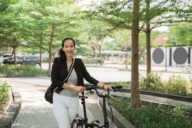Femme travaillant souriante marche sur son vélo pliant à travers le parc