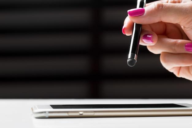 Femme travaillant avec un stylo sur un téléphone mobile intelligent