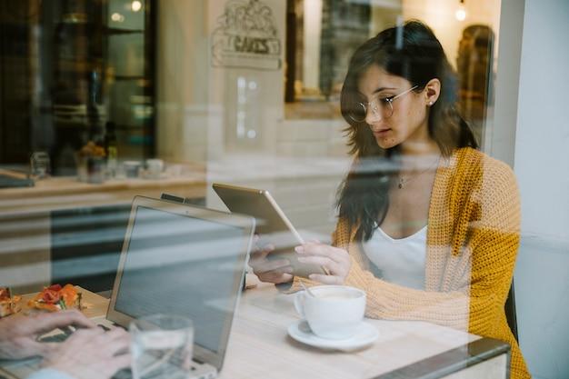 Femme travaillant avec tablette à la table du café