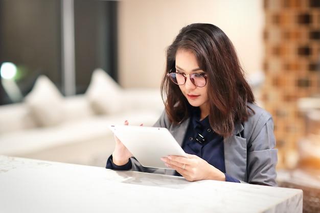 Femme travaillante et charmante avec des lunettes à l'aide d'une tablette (concept de travail à domicile)