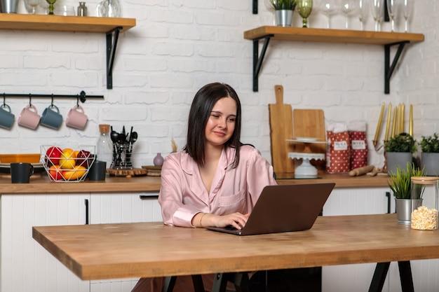 Une femme travaille au bureau à distance de la maison dans la cuisine, assise devant l'ordinateur. formation et travail en ligne à distance. une étudiante se prépare pour les examens.