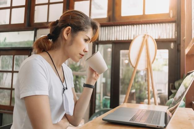 Une femme travaille dans un café-café avec un masque facial sur le cou