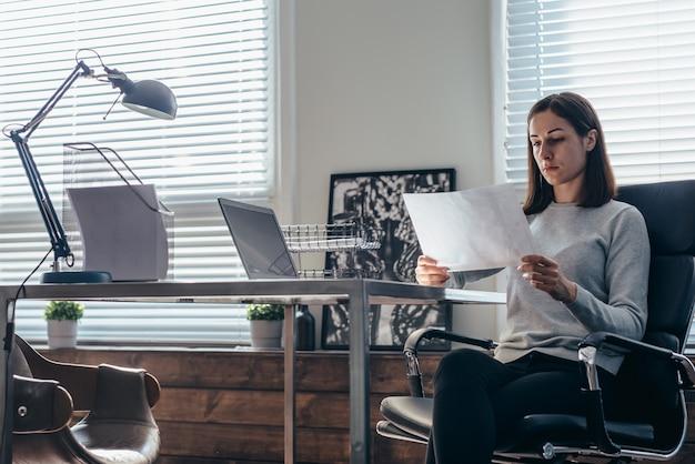 Une femme travaille avec un document assis à son bureau.