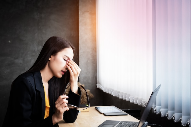 Femme travaille dur, met sa main pour toucher les yeux, fatigue, yeux brûlés d'utiliser un ordinateur portable
