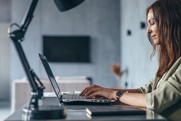 Femme travaille à la maison assis à son bureau avec sa vue latérale d'ordinateur portable