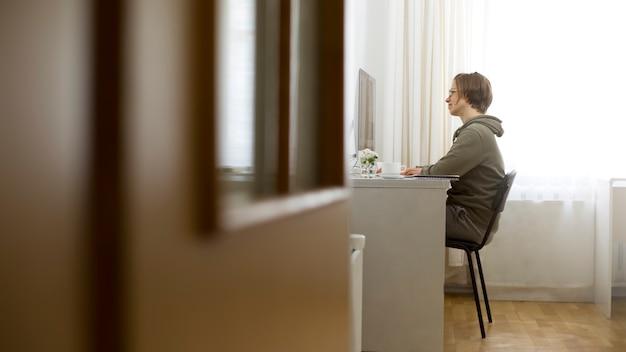La femme travaille à la maison à l'ordinateur.