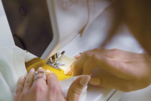 La femme travaille avec un morceau de tissu sur la machine à coudre