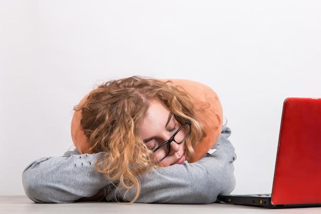 Femme travaille à l'ordinateur avec un oreiller autour du cou sur blanc.