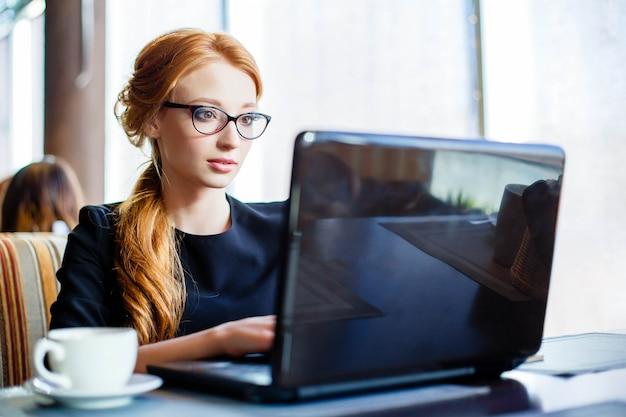 Femme travaille sur l'ordinateur portable au café.