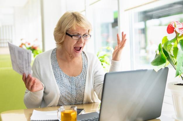 Une femme travaille sur un ordinateur portable dans un café, un bureau. une femme d'âge moyen boit du thé et regarde les informations. elle parle sur internet.