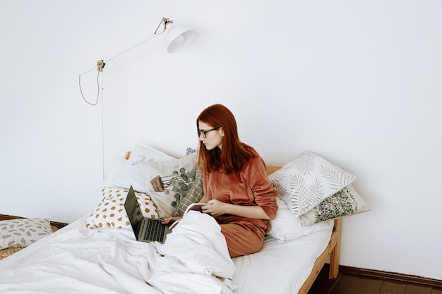 Une femme travaille sur un ordinateur portable dans sa chambre à la maison