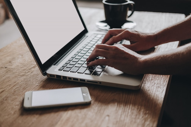 Une femme travaille avec un ordinateur portable et un téléphone avec une tasse de café