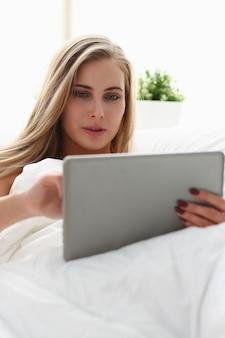 Femme travaille ordinateur portable winh rester au lit tôt le matin