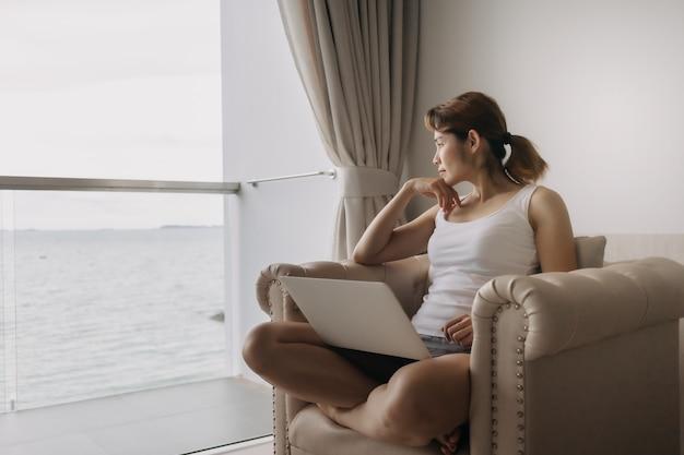 La femme travaille et se détend avec un ordinateur portable sur le canapé concept de travail de l'hôtel