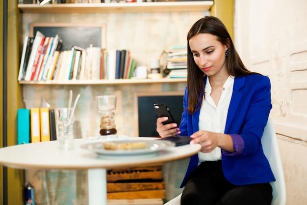 Femme travaille avec un smartphone à la table dans un café
