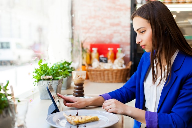 Femme travaille avec une tablette à la table dans un café