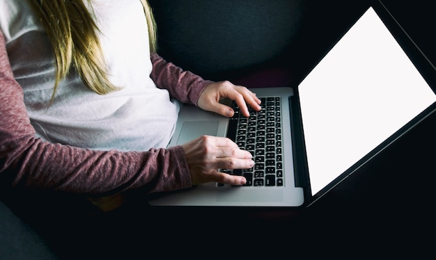 Femme travaille tard assis sur le canapé avec ordinateur portable