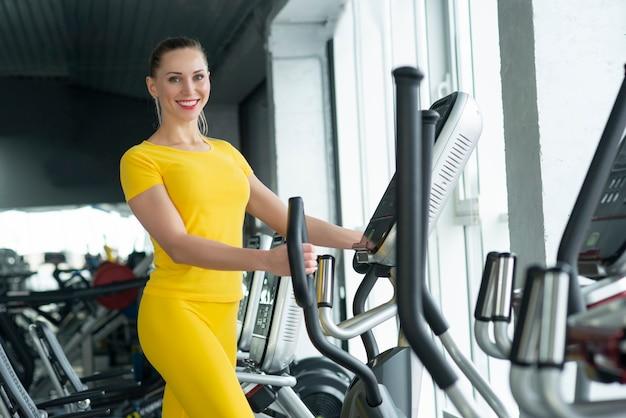 Femme, travailler, elliptique, machine, gymnase