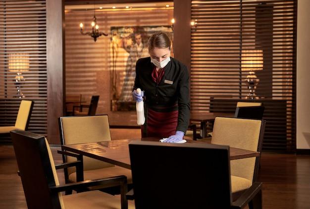 Femme travailleuse dans un masque médical se penchant sur une table de restaurant tout en utilisant un chiffon et un détergent pour le nettoyage