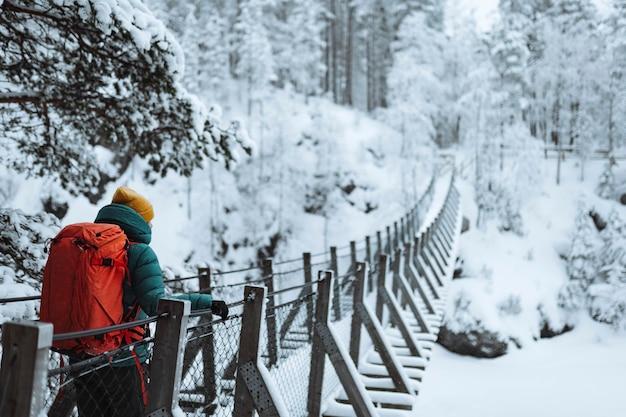 Femme traversant un pont suspendu dans une forêt enneigée, finlande