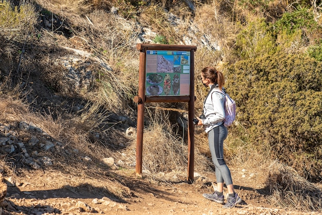 Femme trekking le long d'un chemin dans le parc naturel de peñon de ifach à calpe, portant des vêtements de sport