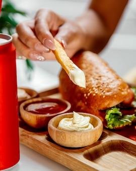 Une femme trempe des frites dans de la mayonnaise