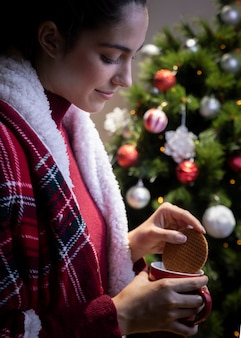 Femme, tremper, biscuit, dans, tasse thé