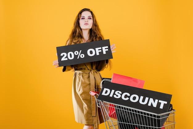 Femme en trench-coat a 20% de rabais sur signe avec chariot rempli de sacs à provisions et ruban de signalisation isolé sur jaune