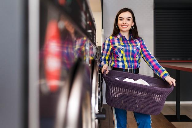 Femme très souriante à la laverie tient un panier de vêtements.