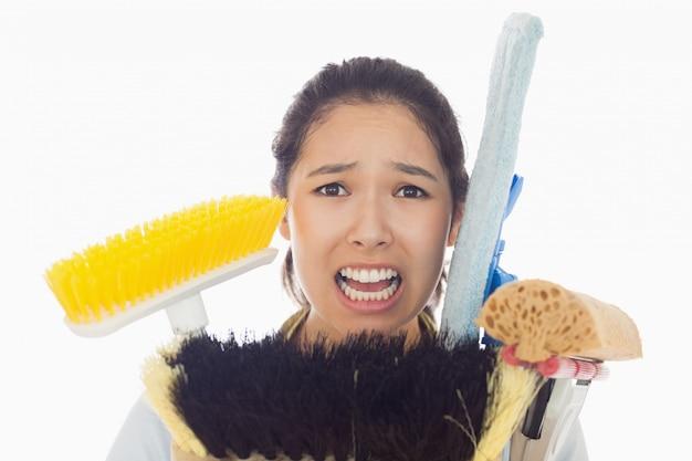 Femme très stressée avec des outils de nettoyage
