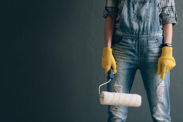 Une femme très volontaire dans un casque de chantier, des mitaines, des lunettes et une combinaison est engagée dans des travaux de réparation et de construction à domicile. concept d'une femme forte et indépendante